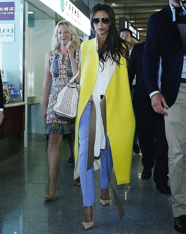 0-victoria-beckhams-beijing-aiport-victoria-beckham-fall-2013-yellow-sleeveless-coat-blue-pants-and-victoria-beckham-leather-tote.jpg